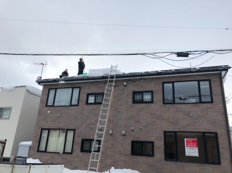 屋根の上で雪下ろし