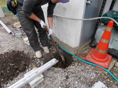 基礎の穴をスコップで掘る