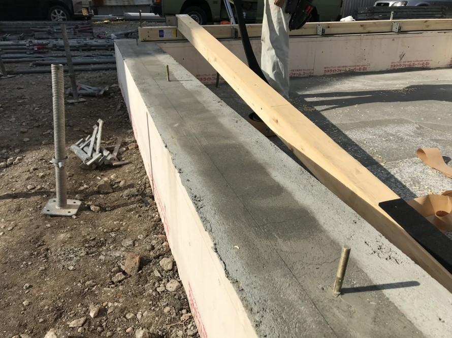 コンクリート基礎から出ている金物と、土台木材に空けた穴を一致させ、差し込みます